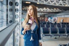 Azafata con bulto de mano y café en aeropuerto imagen de archivo libre de regalías