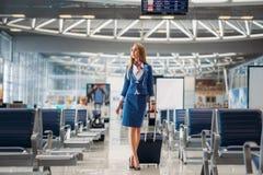 Azafata con el bulto de mano que entra en pasillo del aeropuerto imagen de archivo libre de regalías