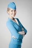 Azafata encantadora In Blue Uniform en Gray Background Imagenes de archivo