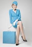 Azafata encantadora In Blue Uniform y maleta en gris Imágenes de archivo libres de regalías