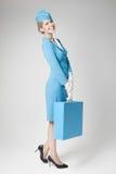 Azafata encantadora In Blue Uniform y maleta en gris Fotografía de archivo