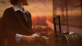 Azafata que celebra los boletos, para vuelo que espera en el aeropuerto, fondo de la puesta del sol metrajes