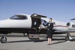 Azafata Standing By Airplane en el campo de aviación Fotografía de archivo
