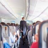 Azafata y pasajeros en el aeroplano comercial foto de archivo libre de regalías