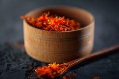 Azafrán Especias indias en cuenco de madera en la tabla de piedra negra Especia e hierbas en fondo de la pizarra cooking imagen de archivo libre de regalías