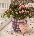 Azalea en la ventana adornada con un corazón decorativo y gotas Foto de archivo