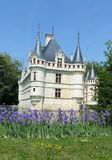 Azay le Rideau chateau. Classic spring time view of French stately home surrounded by small moat with purple iris flowers at edge of grassy bank in foreground royalty free stock images