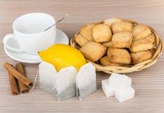 Azúcar, canela, limón, paquetes de té y galletas en cesta Imagenes de archivo
