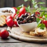 Azeitona com tamato e salsa na tabela de madeira Foto de Stock