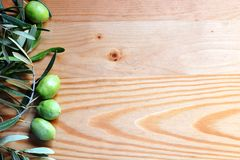 Azeitonas com as folhas verdes no fundo de madeira Imagem de Stock Royalty Free