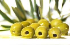 Azeitonas e petróleo verde-oliva na placa Imagem de Stock