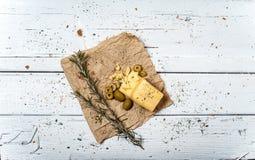 Azeitonas e queijo na tabela retro branca Foto de Stock