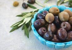 Azeitonas e refeição matinal verde em uma bacia azul em um fundo branco Imagem de Stock