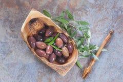 Azeitonas oleosas misturadas na curva de madeira verde-oliva foto de stock