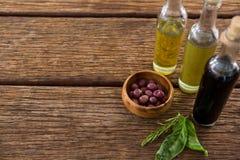 Azeitonas postas de conserva com as garrafas do azeite e do vinagre balsâmico na tabela Imagens de Stock