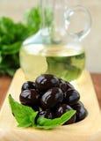Azeitonas pretas e um frasco do petróleo Imagens de Stock