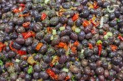 Azeitonas pretas frescas, com pimenta vermelha picante e salsa na venda dentro Imagem de Stock