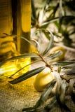 Azeitonas verdes com a garrafa do óleo em uma tabela de madeira Fotografia de Stock Royalty Free