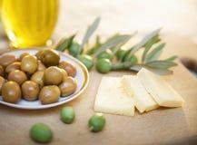 Azeitonas verdes com queijo e ramo de oliveira em uma placa de madeira Imagem de Stock