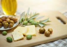Azeitonas verdes com queijo e ramo de oliveira em uma placa de madeira Fotografia de Stock Royalty Free