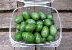 Azeitonas verdes de Cerignola em um recipiente plástico imagem de stock royalty free