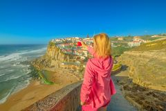 Azenhas do Mar Photographer. Blonde woman takes photo of Azenhas do Mar on Atlantic Ocean. Female tourist takes pictures by mobile phone with Portugal flag of stock photography