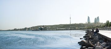 Azerbaijan, Baku with the Flame Towers skyscrapers, television tower and the seaside of the Caspian sea. people resting on the sea stock image