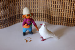 Azerbaijan fairytale character - Dzhyrtdan. Little trikster boy made from color plasticine, feed the pigeon Royalty Free Stock Photo