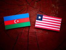 Azerbaijan flag with Liberian flag on a tree stump isolated. Azerbaijan flag with Liberian flag on a tree stump Stock Photography