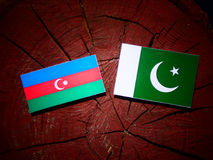 Azerbaijan flag with Pakistan flag on a tree stump isolated. Azerbaijan flag with Pakistan flag on a tree stump vector illustration