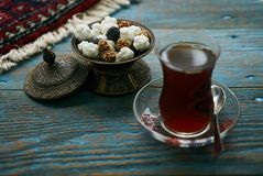 Azerbaijan national pastry Gogal. Novruz holiday with Azerbaijan national pastry Gogal and glass of black tea on rustic wooden table background, Delicious Royalty Free Stock Photos