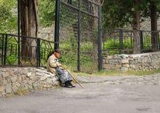 Azerbaijani elderly woman sitting on rocks Stock Photography