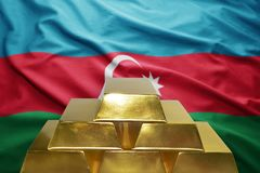 Azerbaijani gold reserves. Shining golden bullions on the azerbaijani flag background Stock Images
