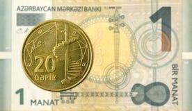 20 azerbaijani qepik coin against 1 azerbaijani manat bank note royalty free stock photos