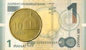 10 azerbaijani qepik coin against 1 azerbaijani manat bank note stock photo