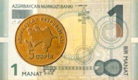 5 azerbaijani qepik coin against 1 azerbaijani manat bank note stock photography