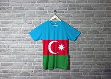 Azerbejdżan flaga na koszula i obwieszenie na ścianie z cegłą deseniujemy tapetę fotografia stock