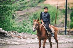 Azeri Junge, der ein Pferd in der Straße auf Kopfstein Huseynov-Straße reitet, die Hauptstraße Gebirgsdorfs Lahic von Aserbaidsch stockfotos