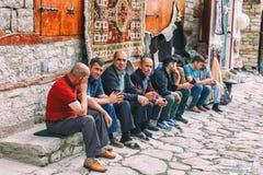 Azeri Männer, die in der Straße auf Kopfstein Huseynov-Straße, die Hauptstraße Gebirgsdorfs Lahic von Azerba sitzen und sprechen lizenzfreie stockfotos