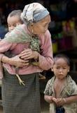 Azië, oude vrouw met kip en kleinzoon Stock Foto