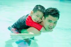 azi? vader en zoon swimmimng in de gelukkige pool, stock foto