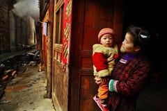 Aziaat met baby in haar wapens, tribunes op landelijke straat. Stock Foto