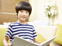 Aziaat weinig boek van de jongenslezing thuis stock fotografie