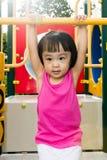 Aziaat weinig Chinees meisje die op horizontale aapbar hangen Stock Fotografie