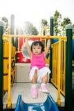 Aziaat weinig Chinees meisje die op horizontale aapbar hangen Stock Foto