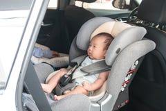 Aziaat weinig die babykind met veiligheidsriem wordt vastgemaakt in de zetel van de veiligheidsauto Royalty-vrije Stock Fotografie