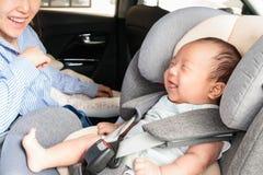 Aziaat weinig glimlachend babykind maakte met veiligheidsriem vast in de zetel van de veiligheidsauto Stock Afbeeldingen