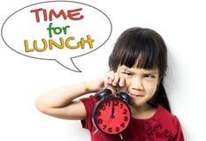 Aziaat weinig jong geitje houdt de klok die zij heeft moeten om voor lunch gaan royalty-vrije stock foto