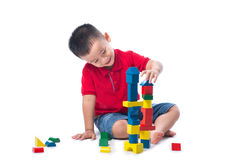 Aziaat weinig jongen die met kleurrijke die blokken spelen, op wit worden geïsoleerd royalty-vrije stock afbeelding