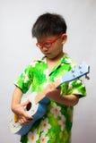 Aziaat weinig jongen het spelen ukelele Stock Fotografie